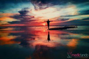 Homem de braços abertos em uma praia durante o pôr do sol, abraçando o crepúsculo.